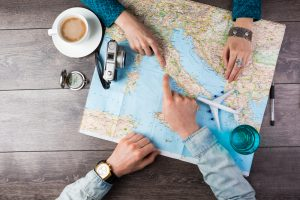 Young,Couple,Planning,Honeymoon,Vacation,Trip,With,Map.,Top,View.